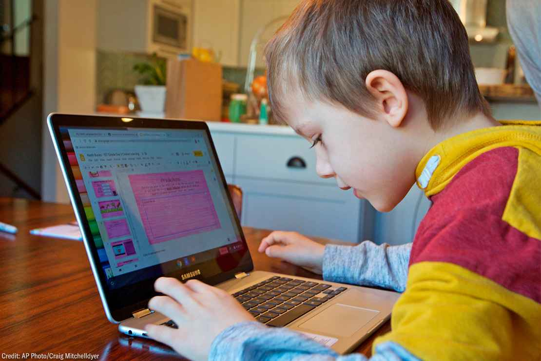 A young child works at home remotely on an online class assignment.