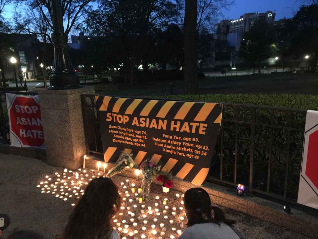 """stop asian hate"" banner and candles at a local vigil"