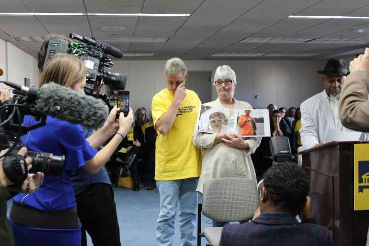 Sandy Davis holds picture of son in front of media