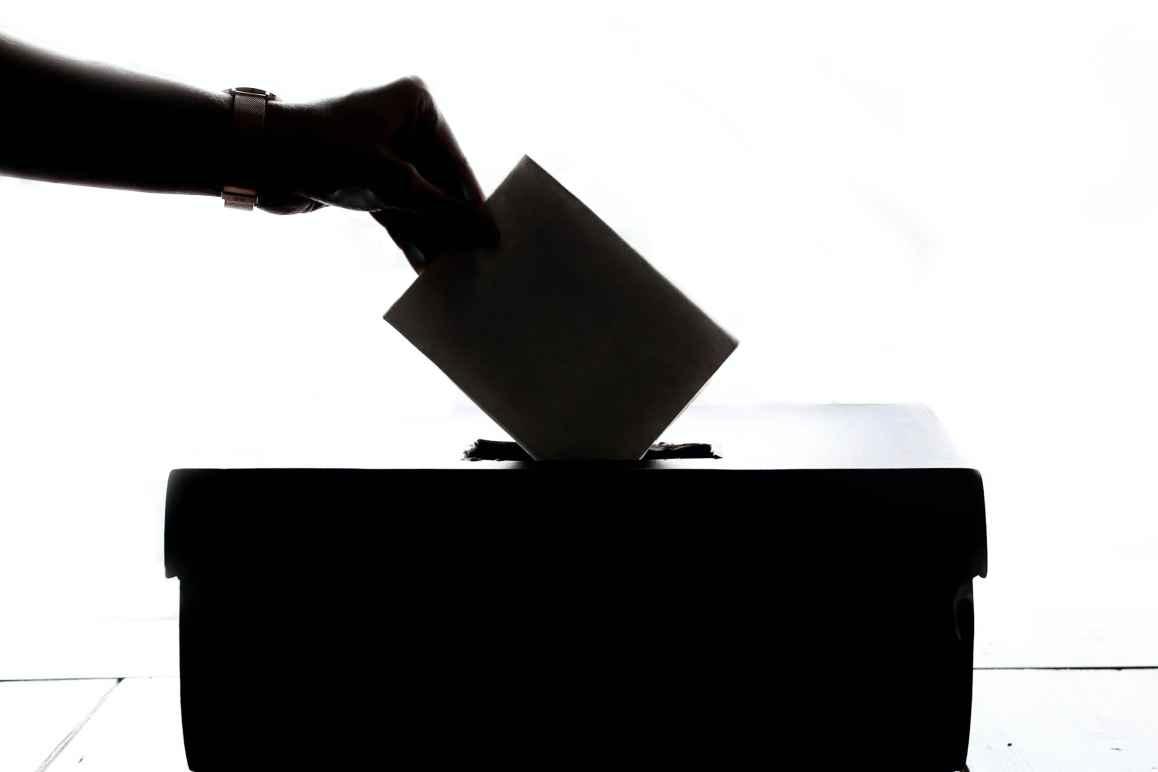 Hand dropping ballot into ballot box.
