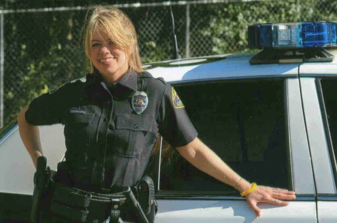 Officer Stephanie Hicks in uniform standing by police car