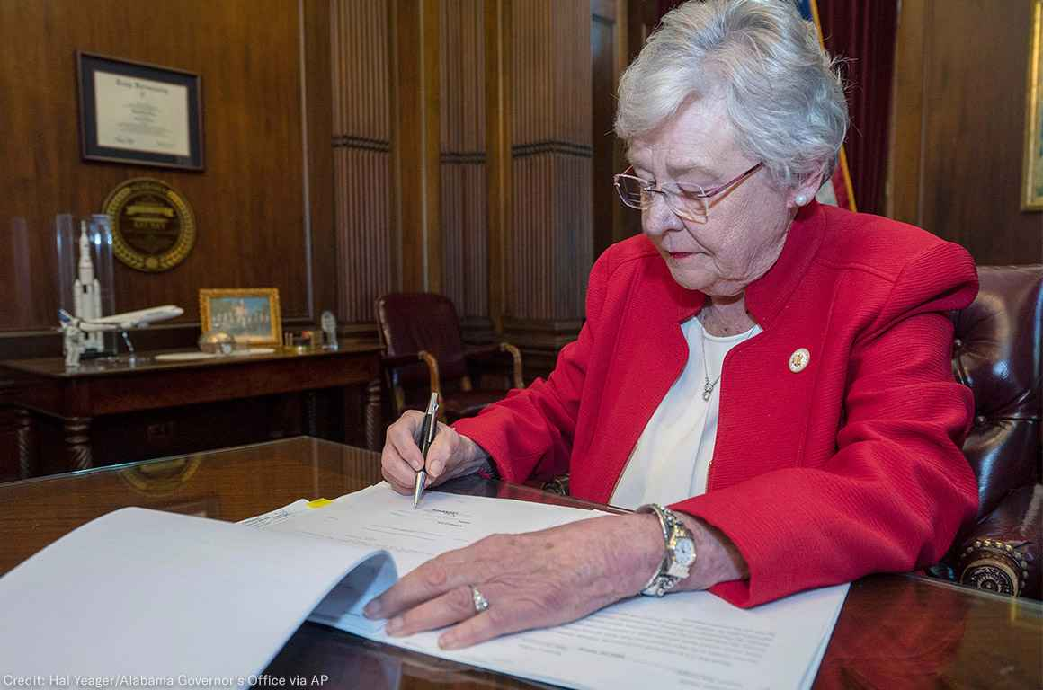 Kay Ivey signing a bill that virtually outlaws abortion in Alabama
