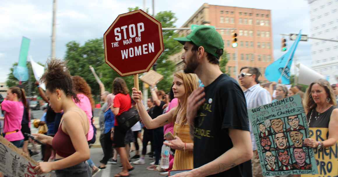 protester marching with sign saying stop the war on women
