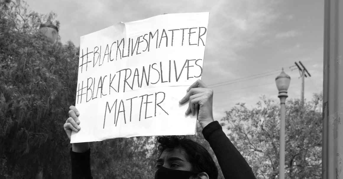 Person with #BlackLivesMatter & #BlackTransLivesMatter Sign - Mike Von